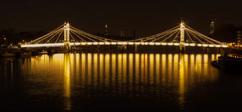 Albert bridge London. Illuminated up Albert bridge in west London with the city scape in the background. The bridge was designed by Rowland Mason Ordish and stock photos