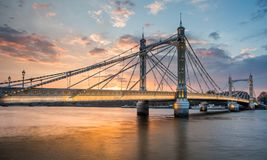 Albert Bridge and beautiful sunset over the Thames, London England UK. Albert Bridge, over the River Thames,Chelsea, London, England, UK, illuminated at night royalty free stock photos