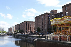 Albert Dock in Liverpool. A photo of a carousel and the waterfront at Albert Dock in Liverpool on a sunny day in the summer Stock Images