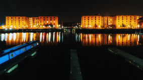 ALBERT DOCKS LIVERPOOL. Night image of liverpool Albert dock lights cityscape canal barges liver building hotels steeple waterfront water still reflection Stock Photos