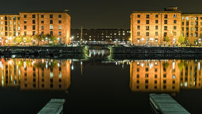 ALBERT DOCKS LIVERPOOL. Night image of liverpool Albert dock lights cityscape canal barges liver building hotels steeple waterfront water still reflection Royalty Free Stock Photo