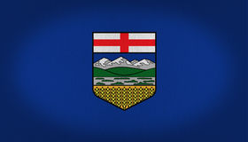 Alberta flag. With a central shield armor, central logo composed by a red cross at the top a central line of mountains and green grass and water over a yellow Royalty Free Stock Photos
