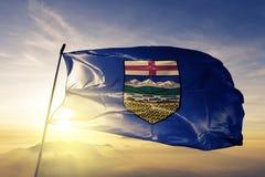 Alberta province of Canada flag textile cloth fabric waving on the top sunrise mist fog. Beautiful stock illustration