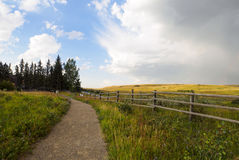 Alberta Ranch pathway with a rain cloud blowing into the blue sky. Nature trail through the Ranchland of Glenbow park in Alberta while the weather was changing Stock Photos