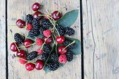 Albicocche, ciliege, gelsi e lamponi sui bordi fotografie stock