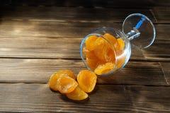 Albicocche secche ambrate in un vetro bluastro di vetro su una superficie di legno fotografie stock