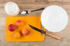 Albicocche sul tagliere, sulla ciotola vuota e sul yogurt in barattolo Fotografia Stock