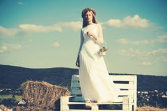 Albino girl with flowers, natural beauty. Woman bride in wedding dress on wooden bench. Sensual woman in wreath on long. Blond hair. Fashion model at sunny blue royalty free stock images