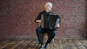 A albino musician with an accordion. A photographer takes pictures of a musician with an accordion against the wall stock footage
