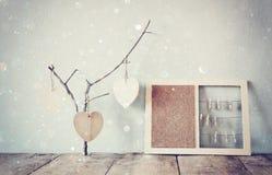 Albo decorativo con le corde ed i cuori di legno di attaccatura e delle mollette da bucato sopra la tavola di legno aspetti per t Immagine Stock
