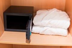 Albornoces frescas y caja fuerte abierta en el estante del armario fotos de archivo