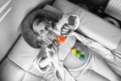 Albornoz blanca que lleva de la mujer embarazada que se relaja y que descansa en casa sobre un sof? blanco imágenes de archivo libres de regalías