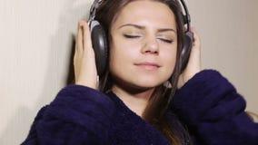 Albornoz de la muchacha en auriculares almacen de video