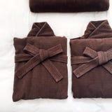 Albornoz del marrón oscuro en cama Fotografía de archivo