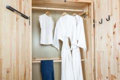 Albornoz y camisa, pantalones en guardarropa de madera Foto de archivo libre de regalías