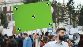Alboroto en ciudad Un muchacho con un cartel en blanco en sus manos para su cámara lenta del título