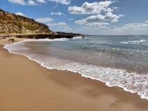 Albufeira beach water& x27;s edge, Algarve Portugal. Albufeira beach waters edge algarve portugal sunny seashore seaside seascape coastline waterline foam stock photography