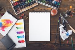 Album in bianco del disegno, colpi variopinti della pittura sulle carte, pitture dell'acquerello e pennelli nel luogo di lavoro Immagine Stock