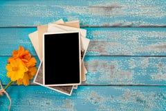 Album in bianco della struttura della foto con il fiore su fondo di legno blu Immagine Stock Libera da Diritti