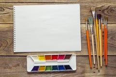 Album d'art et peinture d'aquarelle avec des pinceaux sur vieil en bois images libres de droits