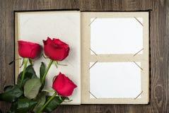 Album fotograficzny i róże na drewnianym tle Zdjęcie Royalty Free