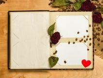 Album fotograficzny i suche czerwone róże na kawowych ziarnach Obraz Stock