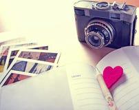Album fotograficzny zamknięty z starą kamerą i fotografiami up Fotografia Stock