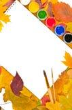 Album mit Lacken und Pinseln in einem Feld der Blätter Stockbild