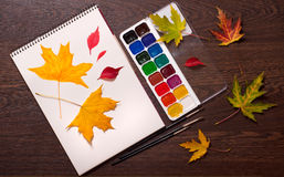 Album, paints, brushes and autumn leaves Royalty Free Stock Photography