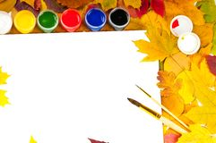Album with paints and brushes in a frame of leaves. White sheet of paper with paints and brushes on the background of autumn leaves Royalty Free Stock Photos