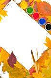 Album with paints and brushes in a frame of leaves. White sheet of paper with paints and brushes on the background of autumn leaves Stock Image