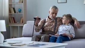 Album photos de observation de grand-papa avec le petit-fils, rappelant des histoires de la jeunesse heureuse photos stock
