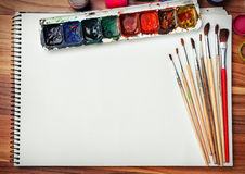 Album for sketches, watercolor paints and brushes Royalty Free Stock Images