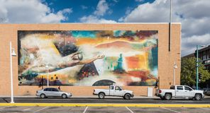 Route 66 Dream Mural. Albuquerque, New Mexico / USA / April 1, 2016: Dreamy mountain scene mural on red brick building framed by white trucks Royalty Free Stock Photo