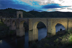 The Alcántara Bridge at sunset 2. The Alcántara Bridge (also known as Puente Trajan at Alcantara) is a Roman stone arch bridge built over the Tagus River at Stock Images