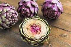 Alcachofa fresca púrpura grande tres y una mitad en fondo de madera imagen de archivo