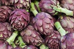 Alcachofas púrpuras frescas en el mercado vegetal imagen de archivo libre de regalías