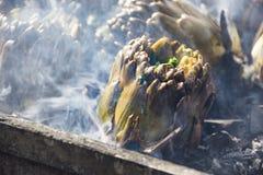 Alcachofas que cuecen en los carbones calientes Fotografía de archivo