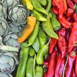 Alcachofas y pimientas en venta en un mercado Foto de archivo