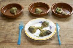 Alcachofras do coração em uma série de pratos da cerâmica Foto de Stock