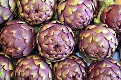 Alcachofras maduras grandes típicas crescidas no campo para a venda no mercado local, textura do fundo Imagem de Stock Royalty Free