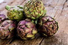 Alcachofras roxas frescas no fundo de madeira rústico escuro fotos de stock royalty free