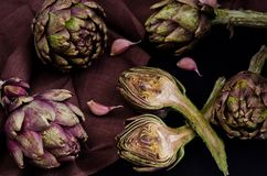 Alcachofras roxas frescas no fundo preto imagens de stock royalty free