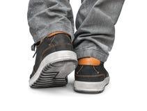 Alcançando homens do pé em calças de brim e em sapatas cinzentas da rua Fotos de Stock