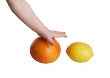 Alcances de la mano de los niños para la fruta Imagen de archivo