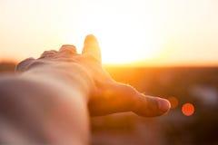Alcances de la mano para el sol Foto de archivo libre de regalías