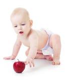 Alcances do bebê para uma maçã Imagens de Stock