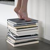 Alcangando um livro na biblioteca Imagens de Stock