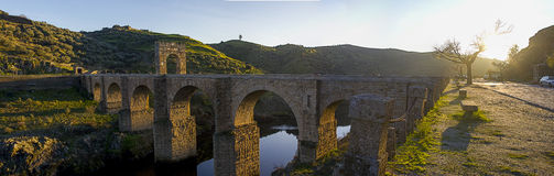 The Alcantara Bridge at Alcantara, Spain. The Alcantara Bridge is a Roman stone arch bridge built over the Tagus River at Alcantara, Spain Stock Image