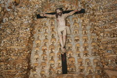 Alcantarilha Chapel. Chapel in Alcantarilha, Portugal, that features walls of 1500 monks' skulls and thigh bones.  Shown with figure of Jesus on crucifix Royalty Free Stock Image